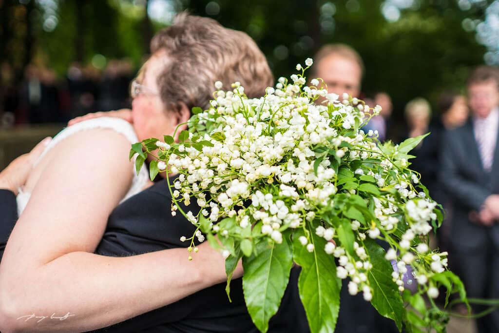 umarmung braut hochzeitsfotografie bach der trauung hochzeitsfotograf hanstedt gäste kapelle glückwünsche