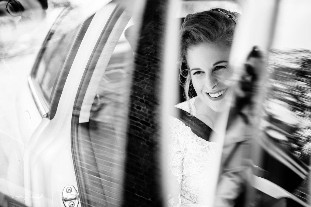 schwarz weiß braut steigt aus dem auto hochzeit vor der trauung braut bräutigam wasserturm lüneburg standesamt